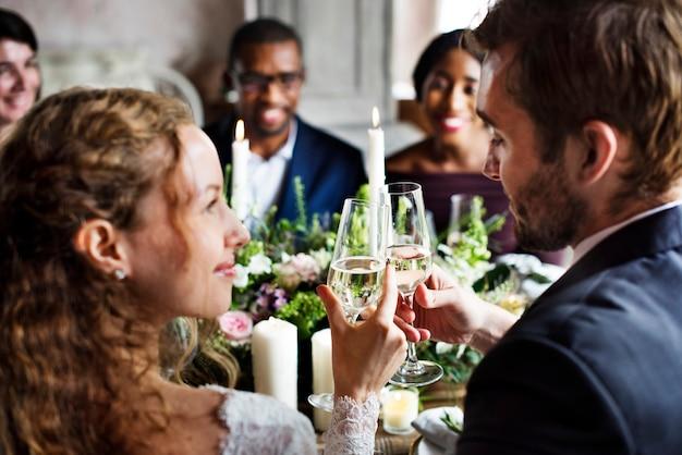 Les mariés griller avec des verres à vin lors d'une réception de mariage