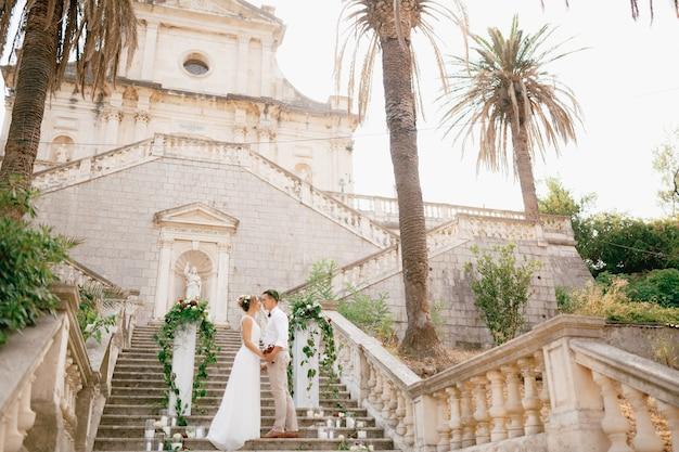 Les mariés en guirlandes se tiennent serrés dans les escaliers