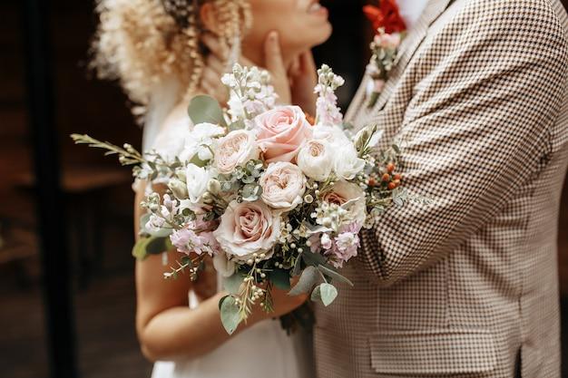 Les mariés le jour du mariage s'embrassent et montrent leur amour avec un bouquet de fleurs roses