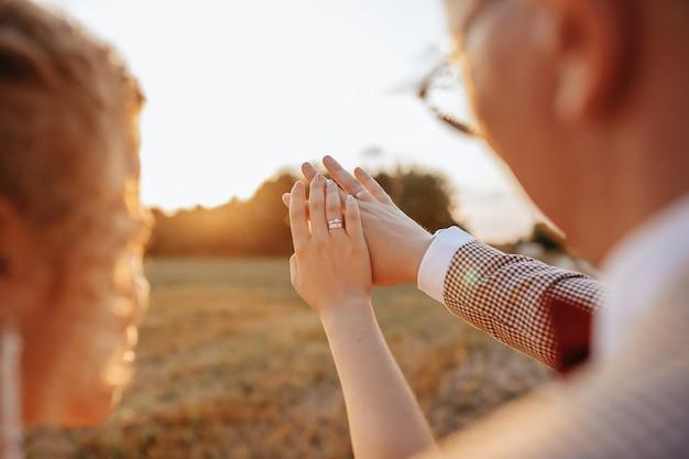 Les mariés le jour du mariage s'embrassent et regardent les anneaux au coucher du soleil