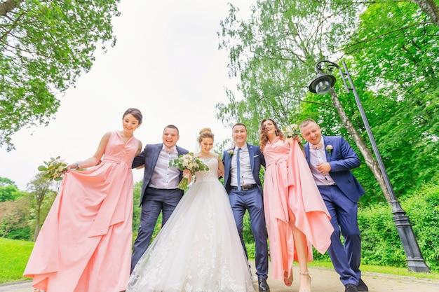 Les mariés avec les meilleurs amis marchent et s'amusent au parc verdoyant.