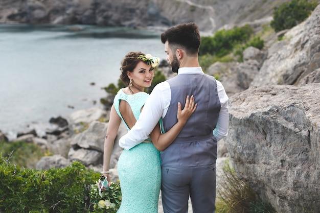 Les mariés sur la nature dans les montagnes près de l'eau. costume et robe couleur tiffany. marchez main dans la main.