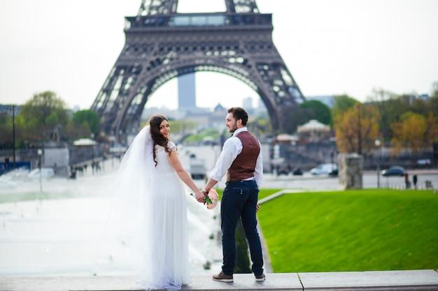 Les mariés passent un moment romantique le jour de leur mariage à paris, devant la tour eiffel