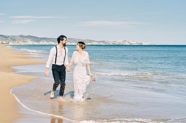 Les mariés qui courent le long de la plage se tenant la main et souriant joyeusement célébrant leur mariage.