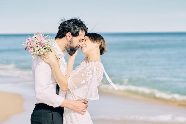 Les mariés s'embrassant sur la plage célébrant joyeusement leur mariage