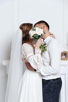 Les mariés se cachaient derrière un bouquet de fleurs, s'embrassant. séance photo de mariage dans une pièce douillette.