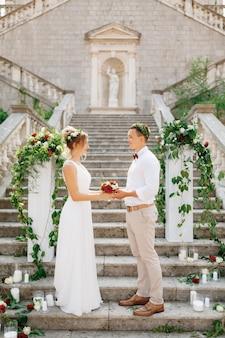 Les mariés se tiennent sur les escaliers
