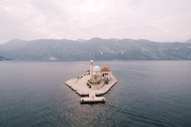 Les mariés se tiennent sur l'île près de la chapelle notre dame des rochers monténégro vue aérienne