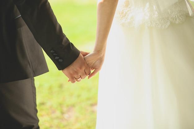 Les mariés se tiennent la main et marchent.