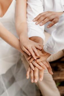 Les mariés se tiennent tendrement la main entre l'amour et les relations