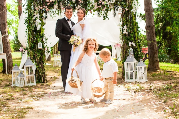Les mariés sourient après la cérémonie de mariage. enfants adorables avec des pétales de rose volants dans des paniers