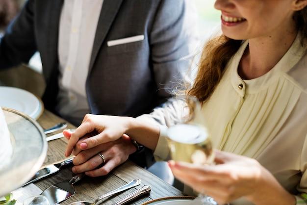 Les mariés tenant les mains sur la réception de mariage