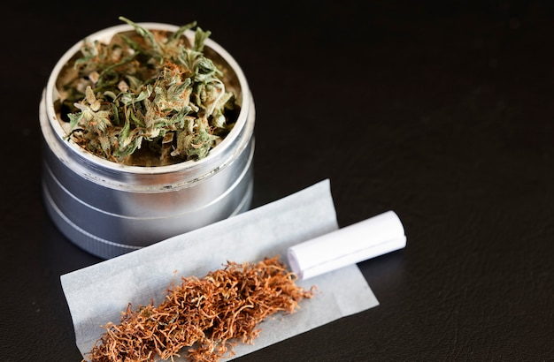 Marijuana sur broyeur avec fond sombre de cigare