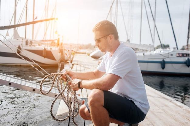 Un marin solide et bien construit est assis en position d'équipe et tient des cordes. il les regarde. guy fait un nœud.