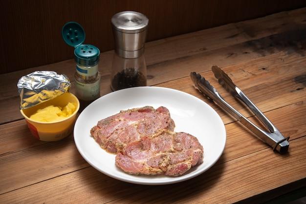 Marinade steak de porc cru dans une assiette blanche à côté de poivre arigano et pinces sur table en bois