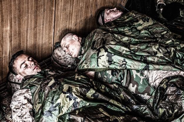 Marines américains fatigués se reposant dans une base ou un camp temporaire, allongés sur le sol en uniforme et en munitions tactiques, recouverts de doublures de poncho et de sacs de couchage, dormant bien après un raid difficile, mission épuisante