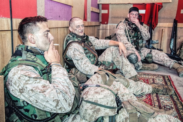 Marines des états-unis en uniforme de camouflage et munitions assis sur le sol à l'avant-poste de combat ou à la base temporaire en mission, parlant dans une atmosphère relaxante, se reposant après une dure journée de service militaire