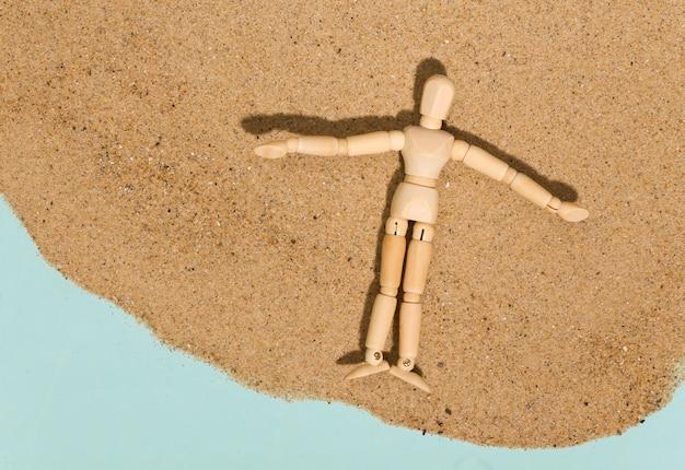 Marionnette en bois bronze sur le sable à une belle journée ensoleillée. concept de vacances à la plage. repos d'été
