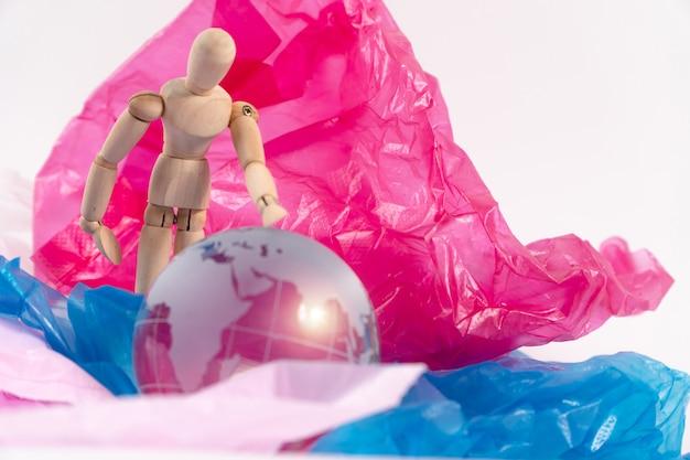La marionnette en bois touche le globe de cristal sur un sac en plastique et se sent inquiète et doit protéger la terre. les déchets plastiques débordent du monde. concept de réchauffement climatique et de changement climatique.