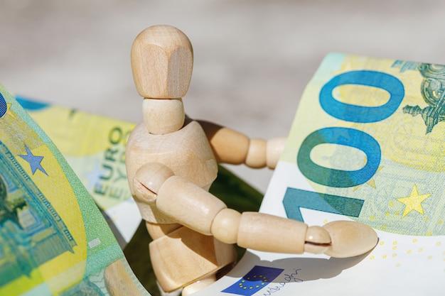 Marionnette factice en bois tenant des centièmes billets en euros. concept d'entreprise