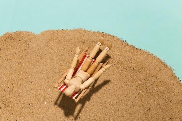 Des marionnettes en bois bronzent sur la chaise longue de plage sur le sable par une belle journée ensoleillée. concept de vacances à la plage. repos d'été