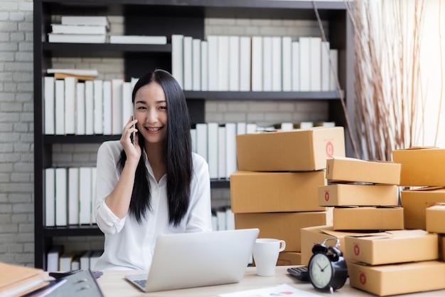 Marketing d'affaires asiatique avec ordinateur portable et boîte de produit sur la table
