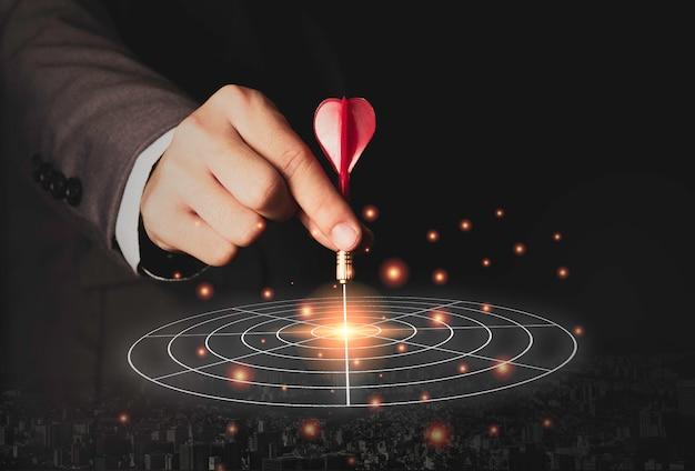 Marketing exécutif main tenant une fléchette rouge placée au centre du plateau cible. objectif d'investissement commercial et concept cible.