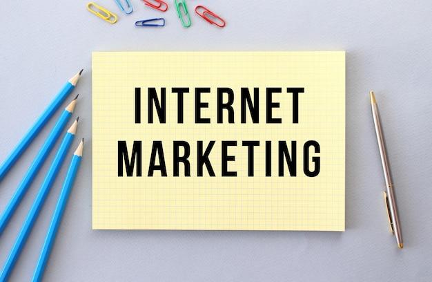 Marketing internet texte dans un cahier sur fond gris à côté de crayons, stylo et trombones.