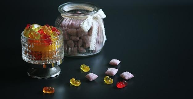 Marmelade dans un vase sur table. bonbons dans un bol sur fond noir. bonbons à la gelée multicolores pour les enfants.