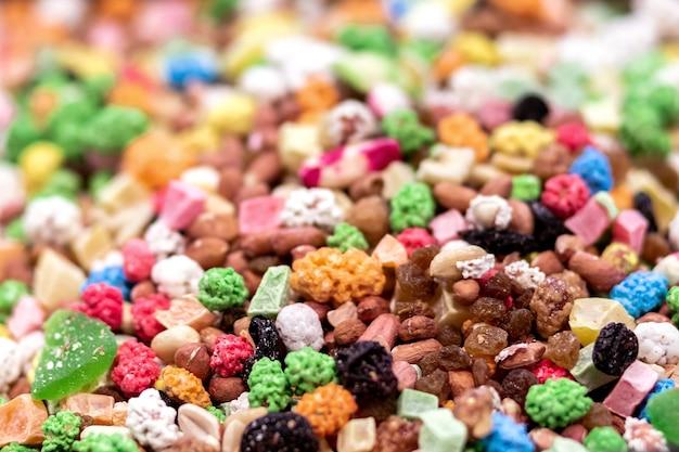 Marmelade, noix, fruits secs, gros plan de raisins secs. fond multicolore avec mise au point sélective