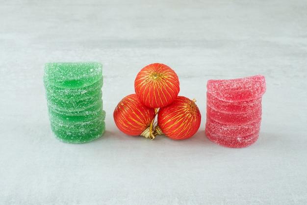 Marmelade de sucre vert et rouge avec des boules de noël rouges sur fond de marbre. photo de haute qualité