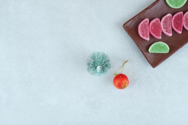 Marmelade sucrée avec boule de noël et arbre sur plaque sombre.