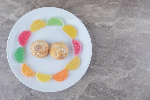 Marmelades autour de petits gâteaux sur un plateau sur marbre