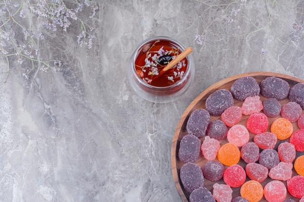 Marmelades dans un plateau en bois avec une tasse de vin brillant