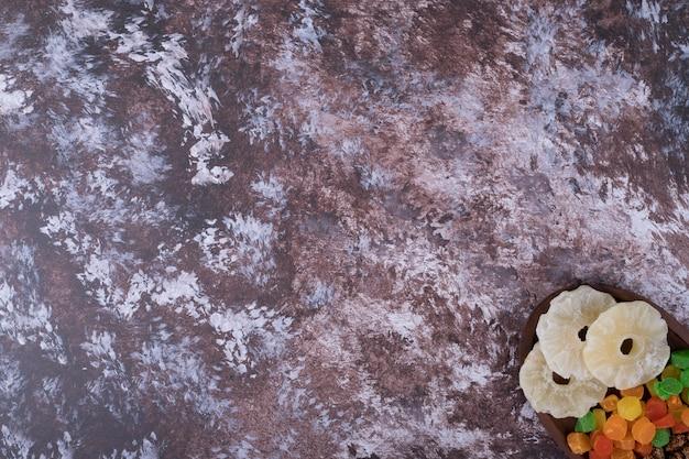 Marmelades et fruits secs en tranches dans un plateau en bois sur le fond