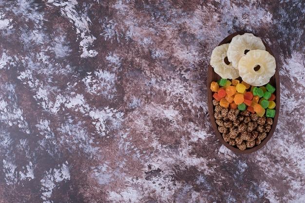 Marmelades et fruits secs tranchés dans un plateau en bois sur la table en marbre