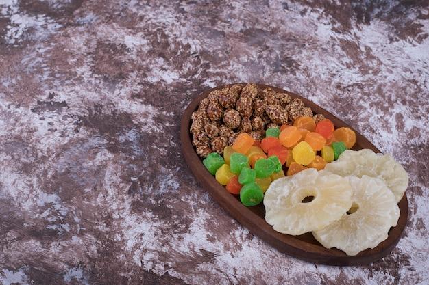 Marmelades et fruits secs tranchés dans un plateau en bois, vue du dessus