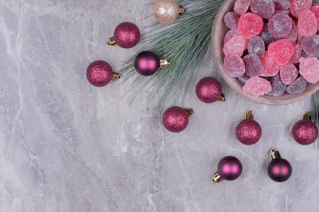 Marmelades violettes dans une tasse en bois avec des boules scintillantes autour