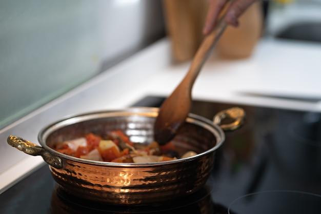 Marmite en cuivre texturé vintage sur kithcen avec main masculine cuisson sur cuisinière légumes avec de la viande.