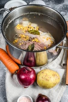 Marmite avec de la viande de bouillon d'os. légumes, cuisson des ingrédients et des épices sur la table de la cuisine. vue de dessus
