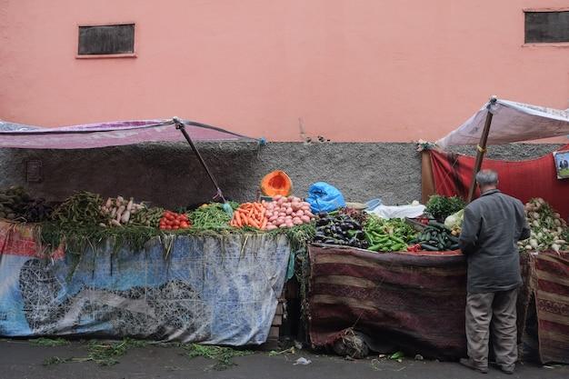 Un marocain achetant des légumes au vieux marché.