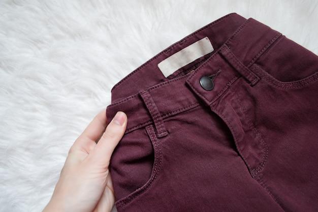 Maroon jeans dans une main féminine. détail. à la mode