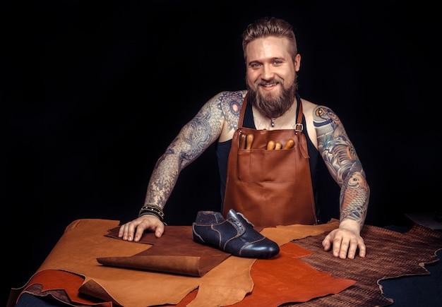 Un maroquinier professionnel crée un produit de cuir de qualité sur le lieu de travail