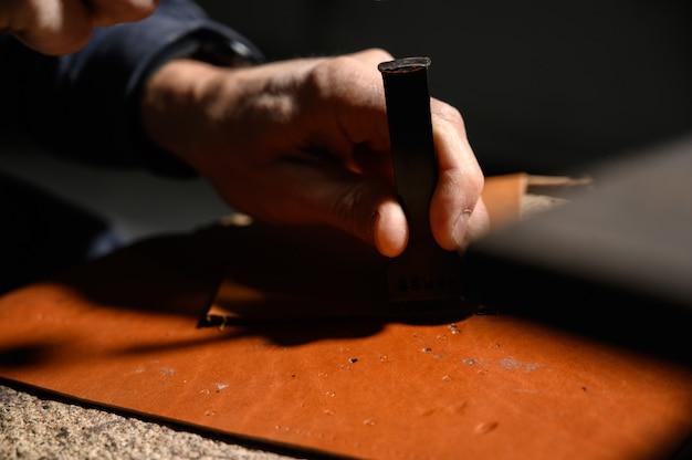 Un maroquinier travaille à la tannerie