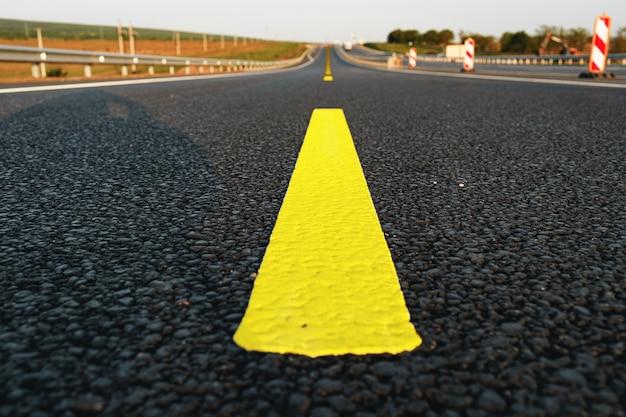 Marquage routier jaune sur route asphaltée close up