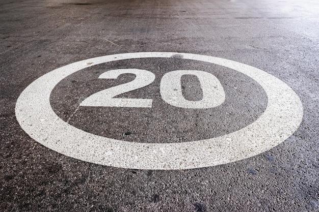 Marque au sol à une vitesse maximale de 20 milles à l'heure sur le sol d'une route résidentielle.