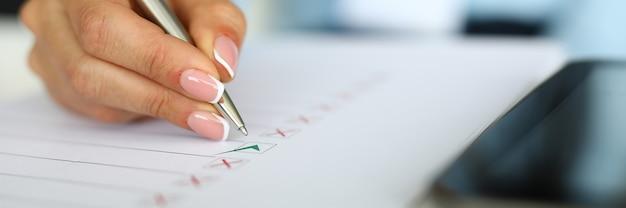 Marque de mains féminines avec stylo sur papier gros plan