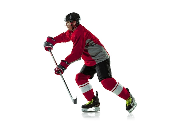 Marquer un but. joueur de hockey masculin avec le bâton sur le court de glace et le fond blanc. sportif portant un équipement et un casque pratiquant. concept de sport, mode de vie sain, mouvement, mouvement, action.