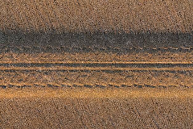 Marques de bande de roulement de pneu sur le sable