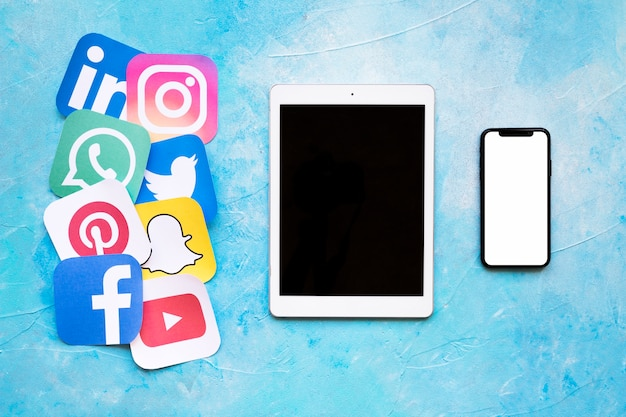 Marques de médias sociaux bien connues imprimées sur papier disposées à proximité d'une tablette numérique et d'un smartphone